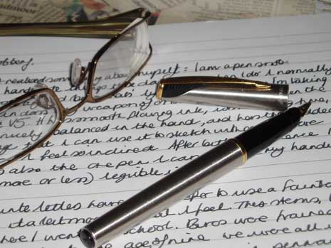 Fountain pen and glasses resting on notebook