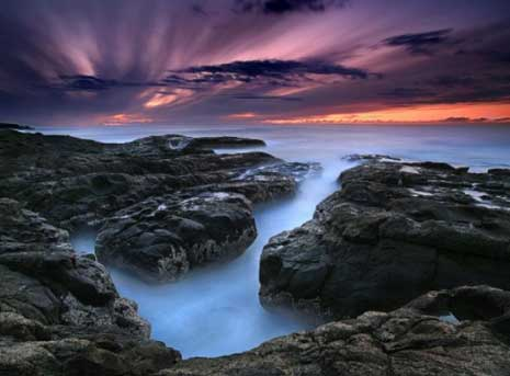 Colorful sky over rock and water