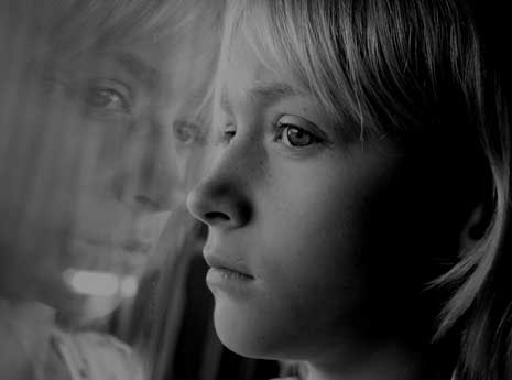 Child looking out a window with reflection