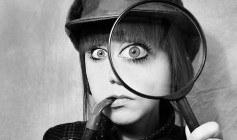 Woman dressed as Sherlock Holmes staring through a magnifying glass