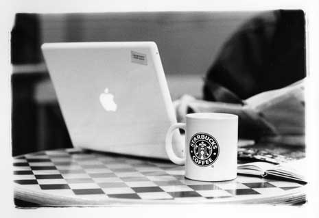 Latop with Apple logo and coffee mug with starbucks