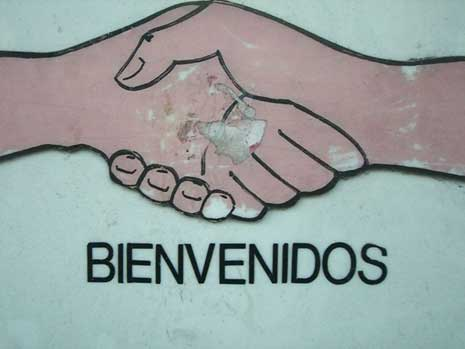 Drawing of two hands shaking with the word bienvenidos below