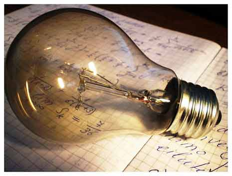 Lightbulb laying on a notebook of ideas