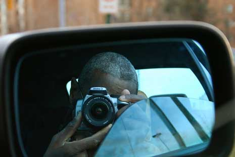 Man taking a picture of himself in sideview mirror