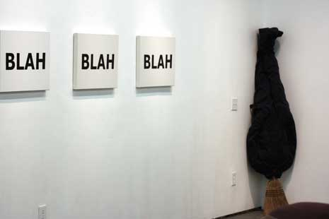 The word 'blah' on 3 canvases and hung on a white wall