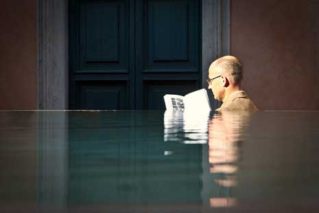 Man reading a book while standing neck deep in water