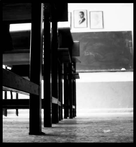 Worm eye view looking down a row of chairs toward the blackboard in an empty classroom