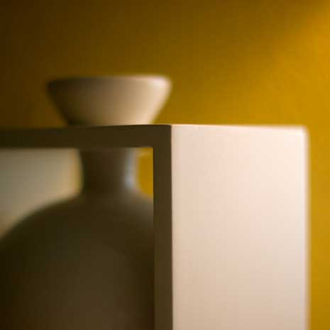 Depth of field shown through a focused table with an unfocused vase behind it.