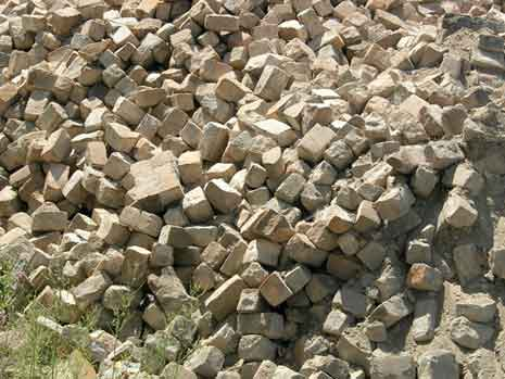 An unorganized pile of bricks on the ground