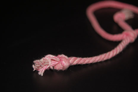 Loose end of a pink rope against a black background