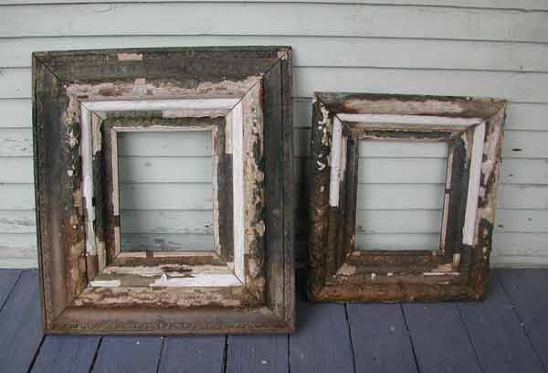 2 old and worn picture frames leaning against a wall