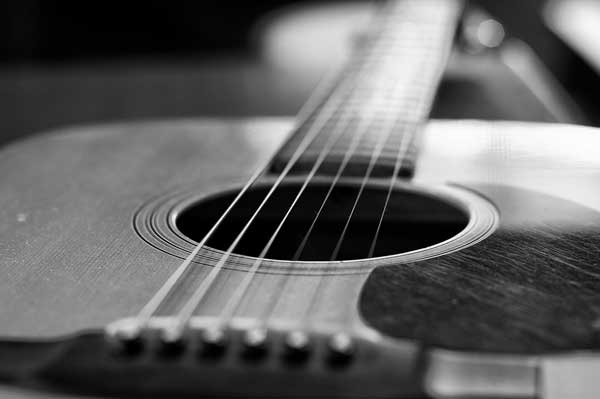An accoustic guitar in black and white
