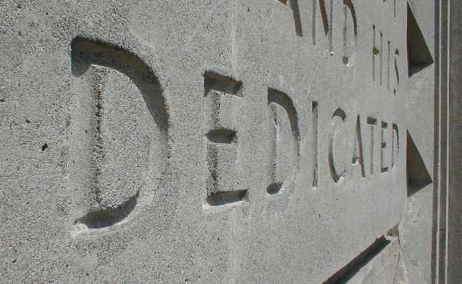 The word 'Dedicated' carved into the stone wall of a building