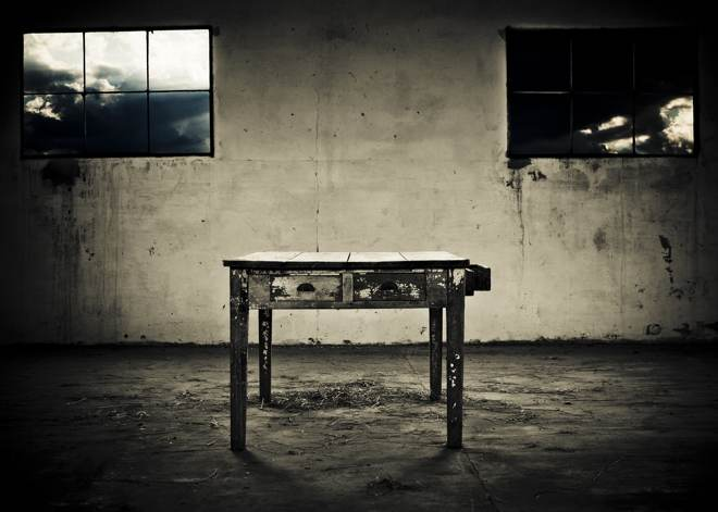A weather table sitting in an empty weathered room