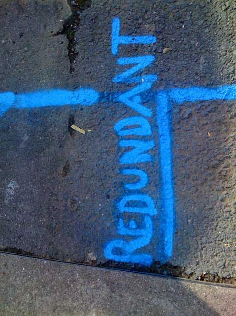 The word redundant spray painted in blue on a wall