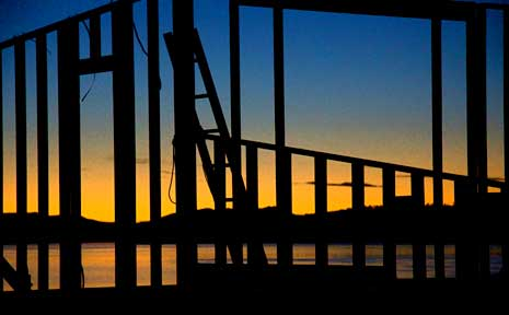 Sunset through the structural framwork of a house being constructed