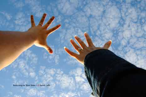 2 hands reaching for the sky