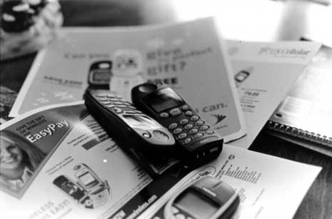 Old mobile phones on a stack of advertisements