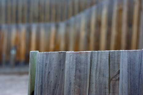 Closeup of a wooden fence with another wooden fence blurred in the background