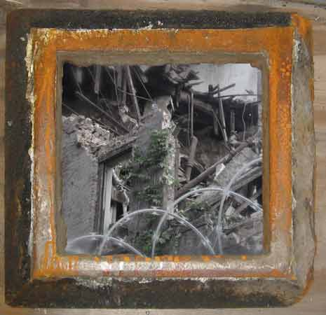 Rusty picture frame around a demolished building