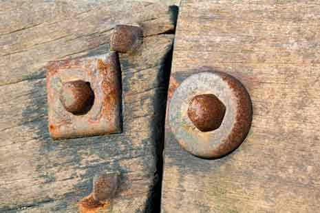 A square washer and a round washer in wooden beams