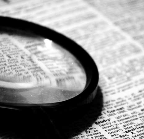 Magnifying glass sitting on text inside dictionary