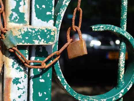 A rusty lock securing a rusty green gate