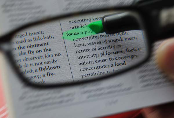 A pair of glasses focusing on the word 'focus' being highlighted in green