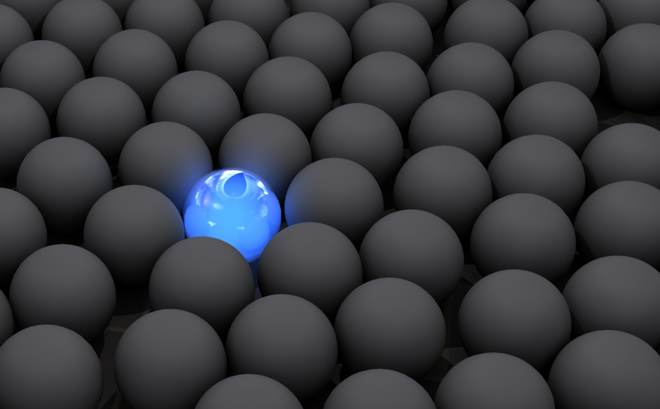 One glowing blue sphere in a sea of dull gray spheres
